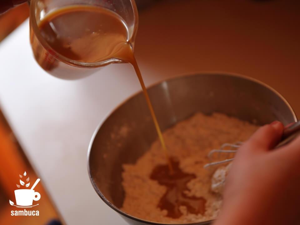 粉のボウルにハチミツ入り牛乳を入れます(サンブーカのケーキ)