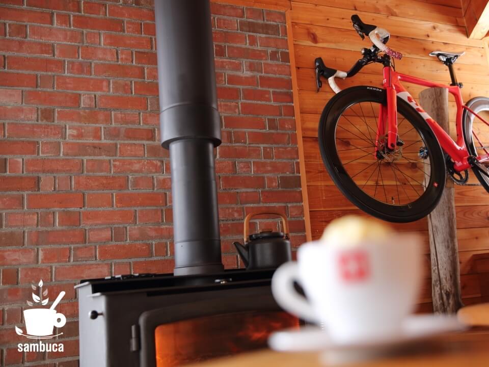 薪ストーブの奥には3Tのロードバイク(ストラーダ)